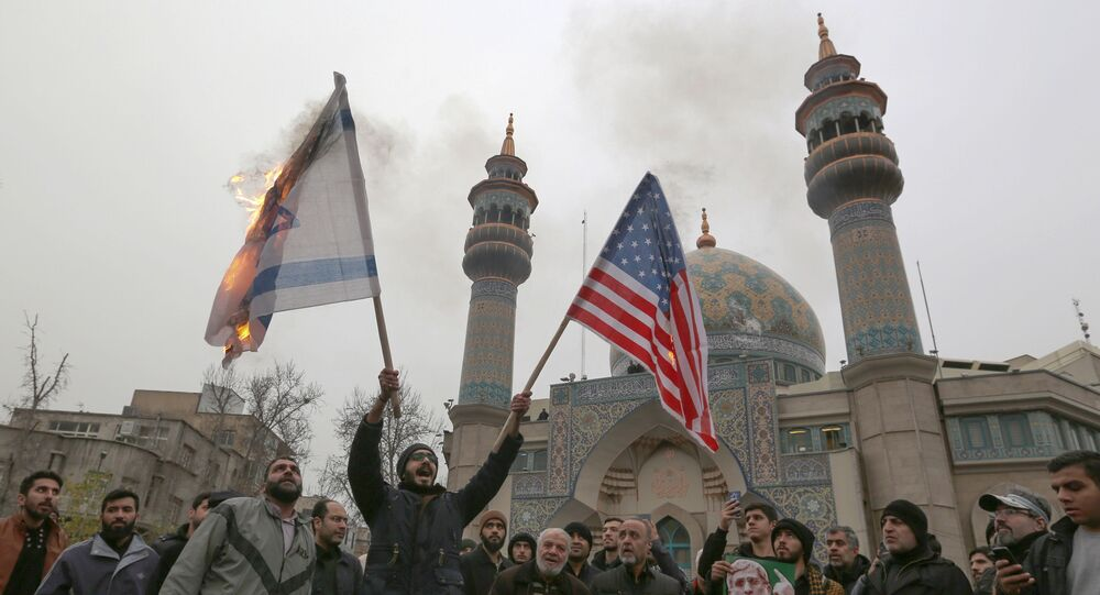Iranians burn an Israeli and a US flag during an anti-US protest over the killings during a US air stike of Iranian military commander Qasem Soleimani and Iraqi paramilitary chief Abu Mahdi al-Muhandis, in the capital Tehran on January 4, 2020.