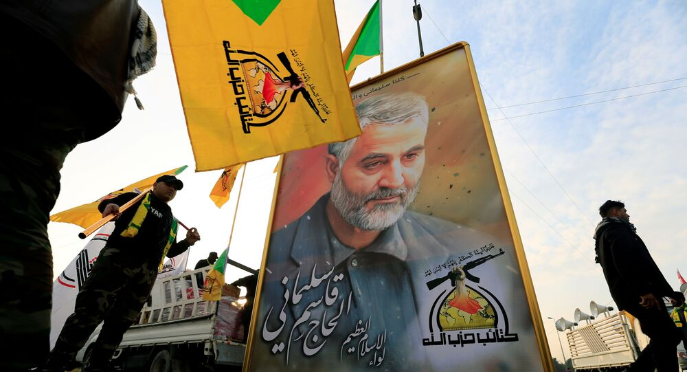 FILE PHOTO: Kataib Hezbollah Iraqi militia hold the picture of the Iranian Major-General Qassem Soleimani, as they gather ahead of the funeral of the Iraqi militia commander Abu Mahdi al-Muhandis, who was killed in an air strike at Baghdad airport, in Baghdad, Iraq, January 4, 2020.