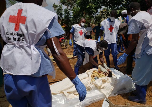 Democratic Republic of Congo's Red Cross members wearing gloves and masks handling dead bodies in Mangina on February 10, 2020, that were brought to the Mangina hospital morgue on February 9, 2020, following an attack on February 8, 2020 in Mangina. - People of Mangina are leaving the city due to the fear of imminent attacks by the Allied Democratic Forces (ADF) in the east of the Democratic Republic of Congo. (Photo by Seros MUYISA / AFP)