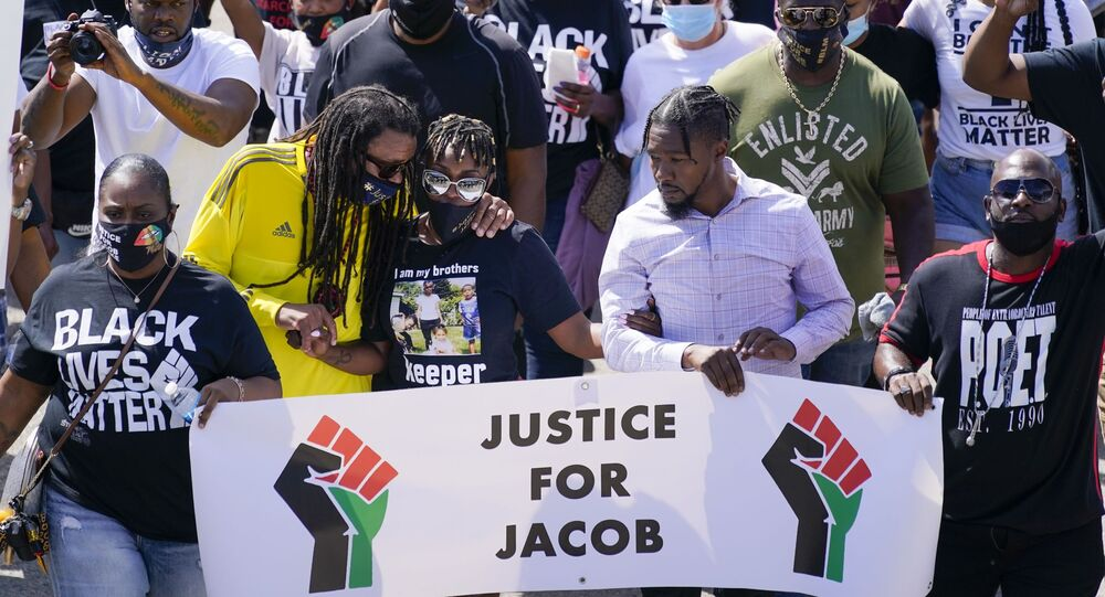 Jacob Blake's sister Letetra Widman and uncle Justin Blake march at a rally for Jacob Blake Saturday, Aug. 29, 2020, in Kenosha, Wis