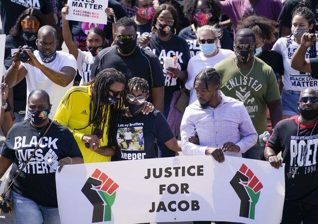 Jacob Blake's sister Letetra Widman and uncle Justin Blake march at a rally for Jacob Blake Saturday, Aug. 29, 2020, in Kenosha, Wis