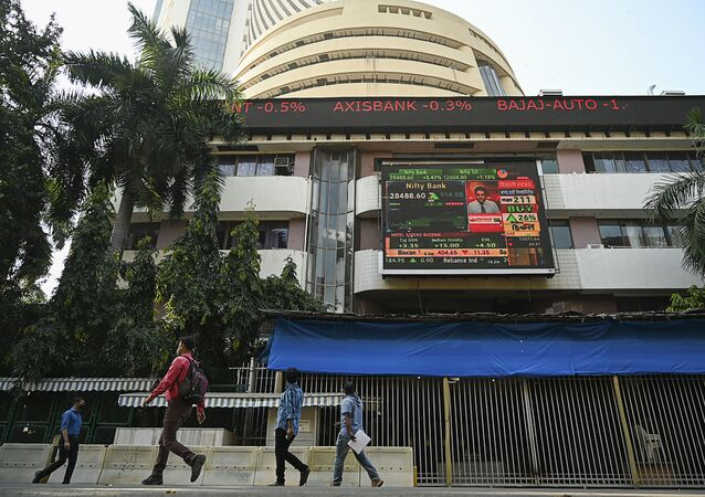 Pedestrians walk past share prices on a digital broadcast outside the Bombay Stock Exchange (BSE) in Mumbai on November 10, 2020.