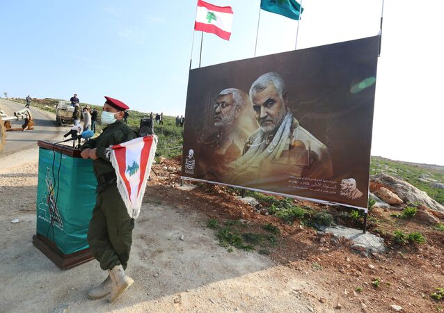 A member of Lebanon's Hezbollah holds a Lebanese flag as he stands in front of a picture depicting senior Iranian military commander General Qassem Soleimani and Iraqi militia commander Abu Mahdi al-Muhandis who were killed in a U.S. attack, during a ceremony marking the first anniversary of their killing, in the southern village of Khiam, Lebanon January 3, 2021. REUTERS/Aziz Taher