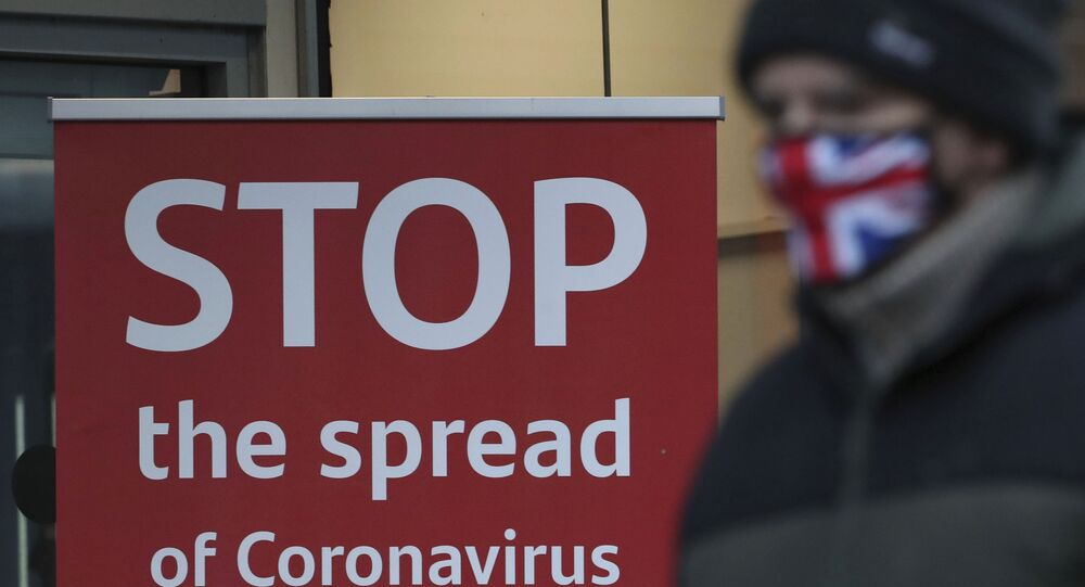 A man wearing a British union flag face mask walks past a coronavirus advice sign outside a bank in Glasgow the morning after stricter lockdown measures came into force for Scotland, Tuesday Jan. 5, 2021.  Further measures were put in place Tuesday as part of lockdown restrictions in a bid to halt the spread of the coronavirus.