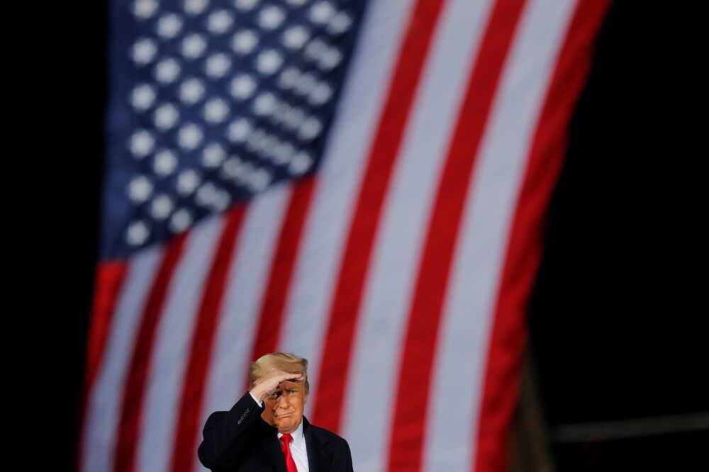 US incumbent President Donald Trump gestures in front of a US flag while campaigning for Republican Senator Kelly Loeffler on the eve of the runoff election to decide both of Georgia's Senate seats, in Dalton, Georgia, US, 4 January 2021.