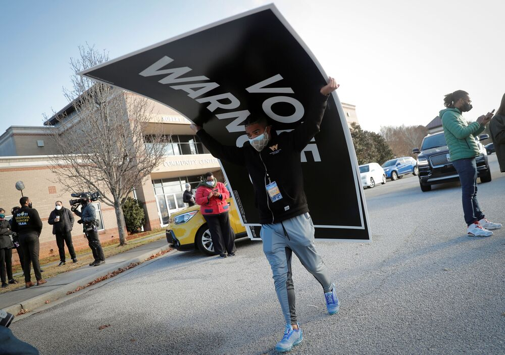 A man carries a sign at a campaign rally for US Senate Democrat candidates Jon Ossoff and the Reverend Raphael Warnock ahead of US Senate runoff elections in Augusta, Georgia, US, 4 January 2021.