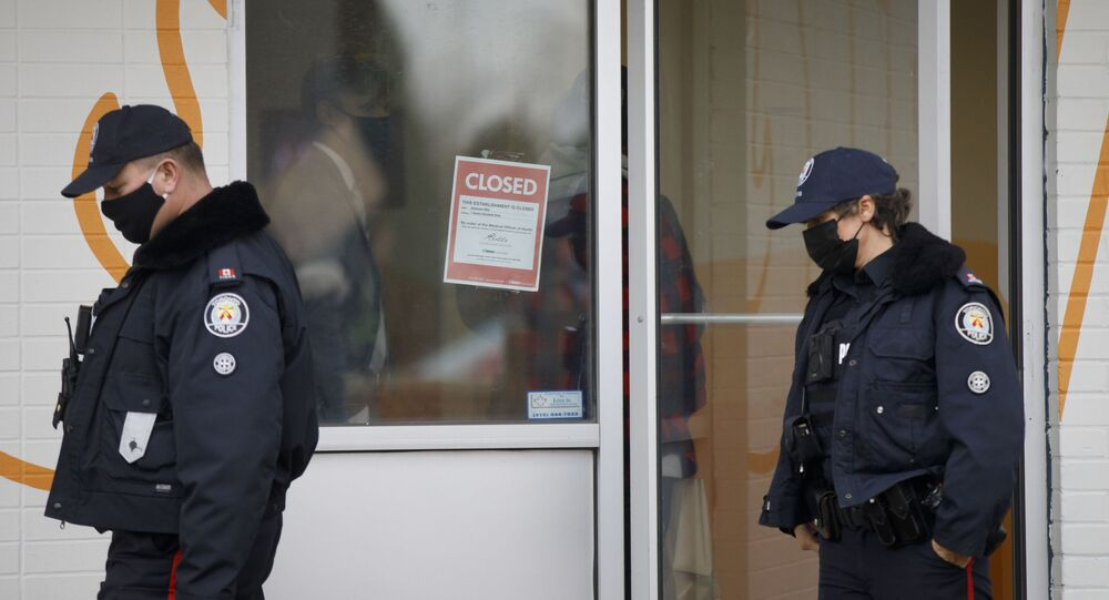 Toronto Police officers walk by a shutdown order on the window of Adamson Barbecue, an Etobicoke business that has defied provincial shutdown orders, on November 25, 2020 in Toronto, Canada.
