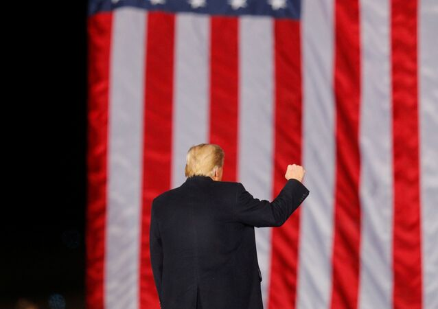 U.S. President Donald Trump gestures in front of a U.S. flag while campaigning for Republican Senator Kelly Loeffler on the eve of the run-off election to decide both of Georgia's Senate seats, in Dalton, Georgia, U.S., January 4, 2021.