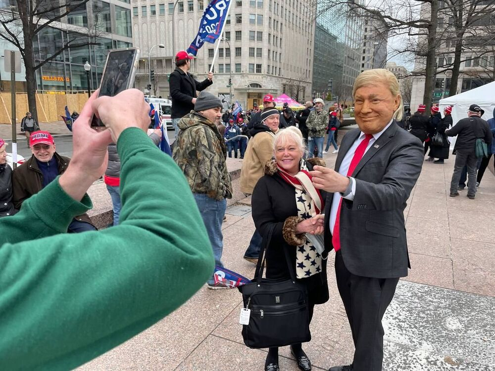 A demonstrator takes a selfie with a person wearing a Trump mask during a rally in Washington DC.