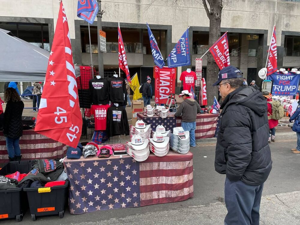 A man looks at caps and hats with pro-Trump slogans during a rally in DC.