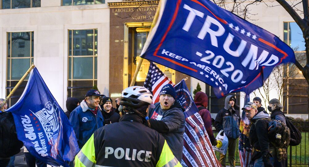 Pro-Trump supporters stand behind police as they argue with counter protesters during a confrontation near Black Lives Matter plaza in Washington, DC on January 5, 2021, on the eve of a rally of supporters of US President Donald Trump to protest the upcoming certification of Joe Biden's Electoral College as president.
