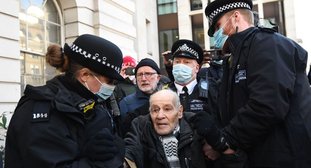 Police arrest a supporter of Wikileaks founder Julian Assange outside Westminster Magistrates court in London as he appears for a bail hearing on January 6, 2021.