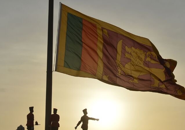 Sri Lankan soldiers stand at attention as their national flag is lowered as part of a daily ceremony at the Galle Face Green promenade in Colombo on July 20, 2018.