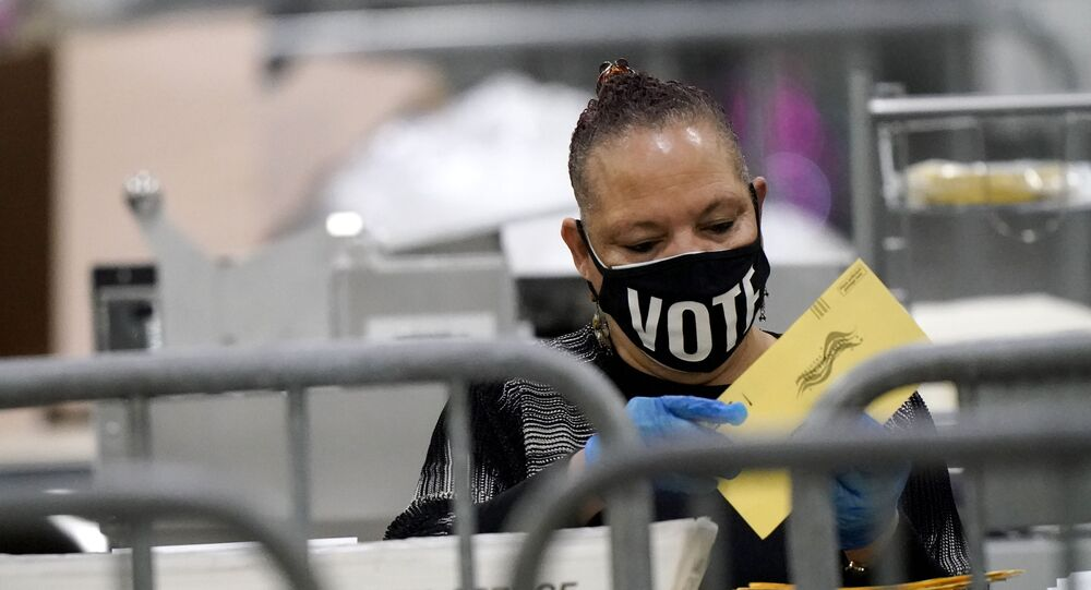 An official counts ballots for Georgia's Senate runoff election at the Georgia World Congress Center on Wednesday, Jan. 6, 2021, in Atlanta.