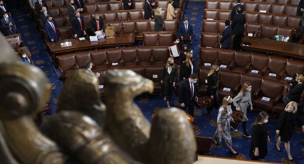Senate pages carry boxes containing Electoral College votes into a joint session of the House and Senate convenes to count the electoral votes cast in November's election, at the Capitol, Wednesday, Jan 6, 2021. (AP Photo/Andrew Harnik)
