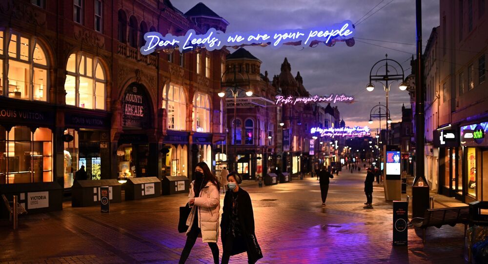 People walk past shops, temporarily closed down due to current coronavirus restrictions, in Leeds, northern England on January 6, 2021, on the second day of Britain's national lockdown to combat the spread of COVID-19.