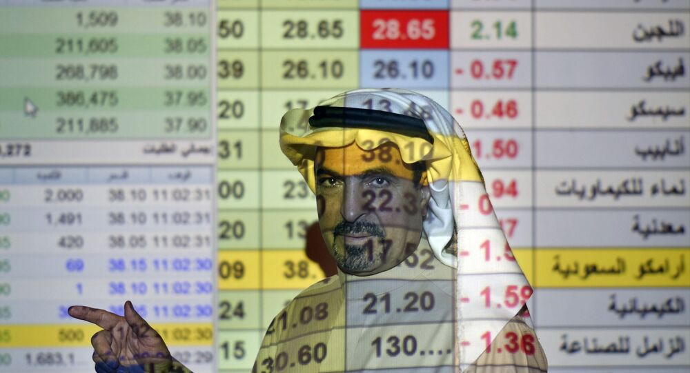 In this Thursday, Dec. 12, 2019, file photo, a trader talks to others in front of a screen displaying Saudi stock market values at the Arab National Bank in Riyadh, Saudi Arabia.