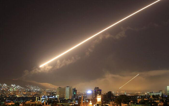 In this April 14, 2018 file photo, Damascus skies erupt with surface to air missile fire as the U.S. launches an attack on Syria targeting different parts of the Syrian capital Damascus, Syria.
