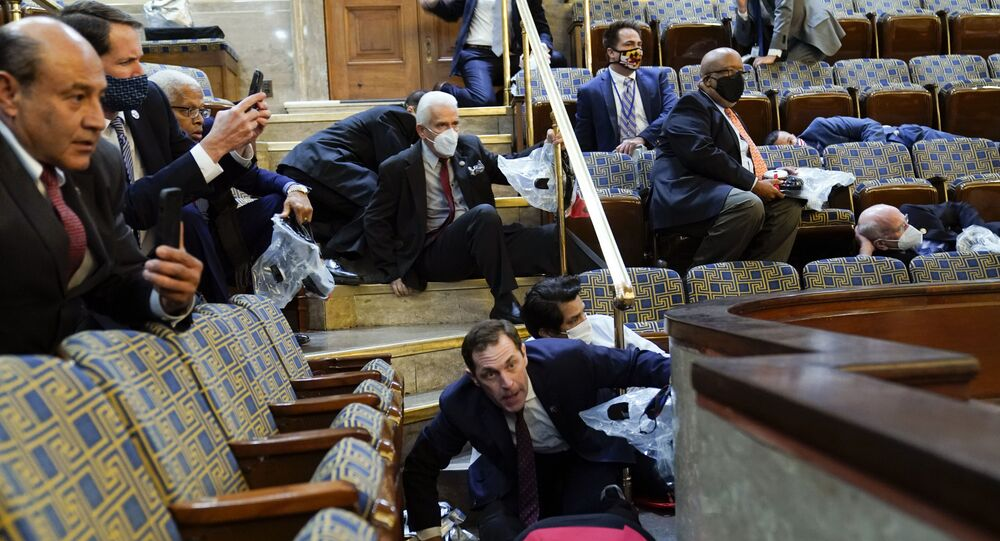 People shelter in the House gallery as protesters try to break into the House Chamber at the U.S. Capitol on Wednesday, Jan. 6, 2021, in Washington
