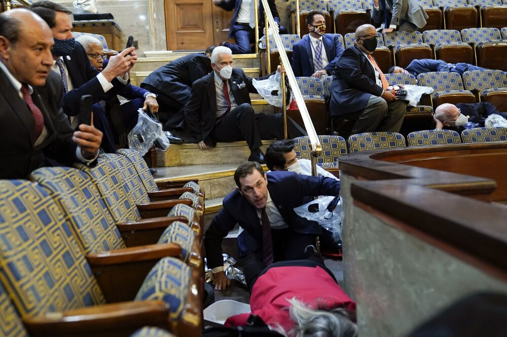 People shelter in the House gallery as protesters try to break into the House Chamber at the U.S. Capitol on Wednesday, 6 January 2021, in Washington
