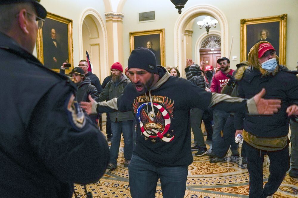 Trump supporters gesture to US Capitol Police in the hallway outside of the Senate chamber at the Capitol in Washington, Wednesday, 6 January 2021