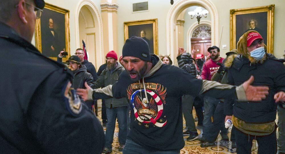 Trump supporters gesture to US Capitol Police in the hallway outside of the Senate chamber at the Capitol in Washington, Wednesday, Jan. 6, 2021