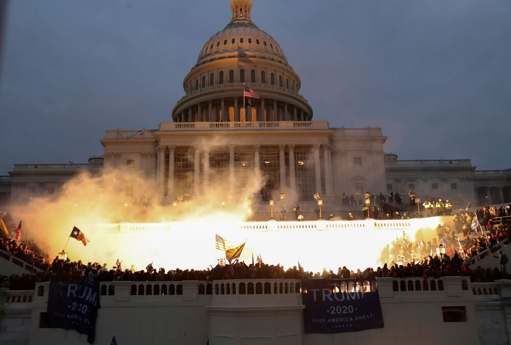 An explosion caused by a police munition is seen while supporters of US President Donald Trump gather in front of the US Capitol Building in Washington, US, 6 January 2021