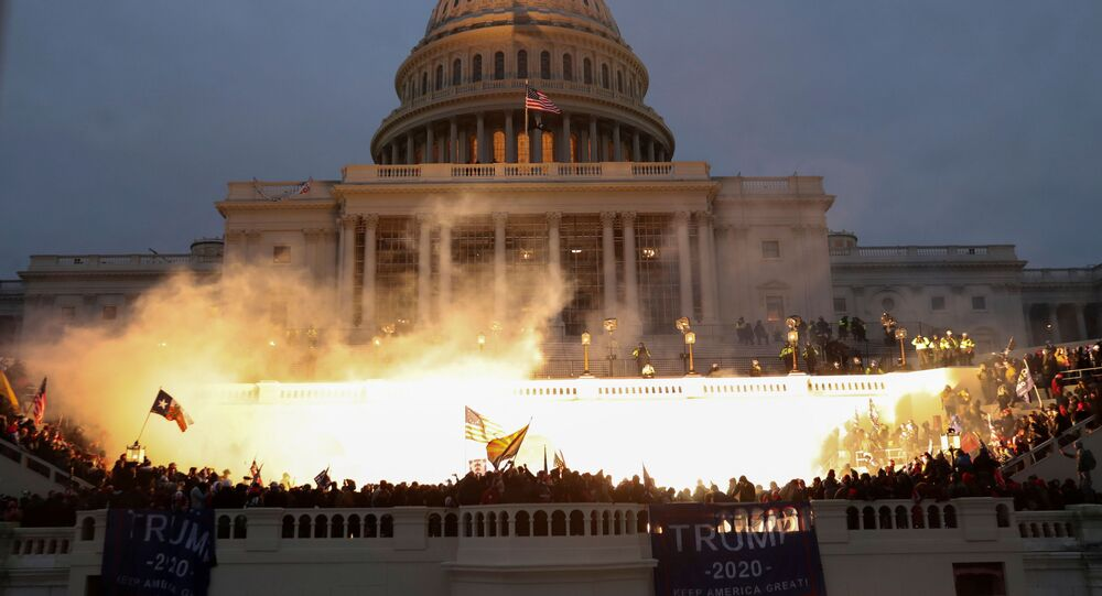 An explosion caused by a police munition is seen while supporters of US President Donald Trump gather in front of the US Capitol Building in Washington, US, January 6, 2021