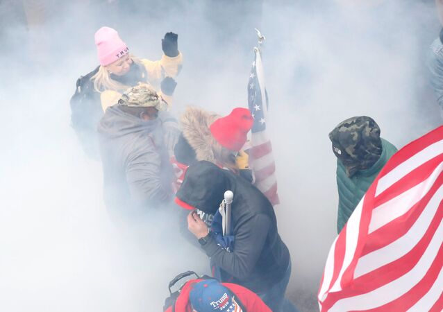 Pro-Trump protesters react amidst a cloud of tear gas during clashes with Capitol police at a rally to contest the certification of the 2020 US presidential election results by the US Congress, at the US Capitol Building in Washington, US, January 6, 2021. REUTERS/Shannon Stapleton