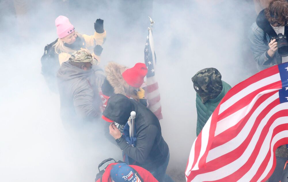 Pro-Trump protesters react amidst a cloud of tear gas during clashes with Capitol police at a rally to contest the certification of the 2020 US presidential election results by the US Congress, at the US Capitol Building in Washington, US, 6 January 2021. REUTERS/Shannon Stapleton