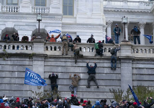 Supporters of President Donald Trump climb the west wall of the the US Capitol on Wednesday, Jan. 6, 2021, in Washington