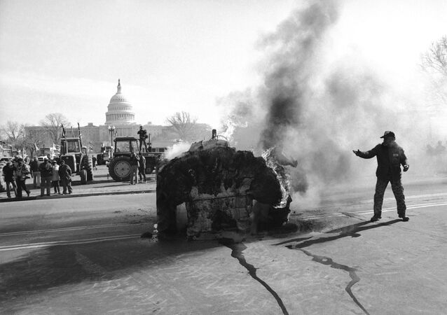 A farmer stands near a tractor which has a blazing ball of cotton on it near the Capitol in February 1979.
