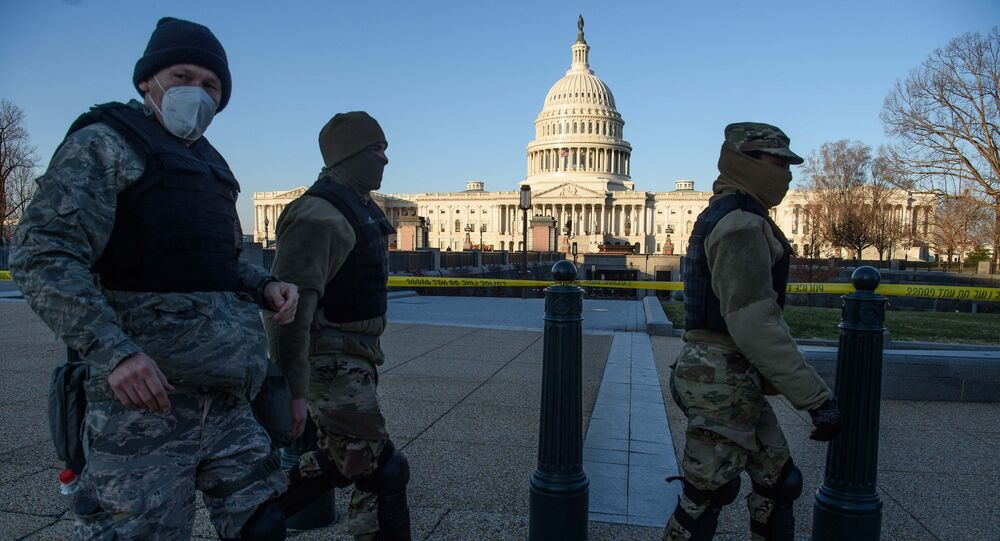Members of the DC National Guard walk past the US Capitol in Washington, DC, on January 7, 2021, one day after supporters of outgoing President Donald Trump stormed the building.