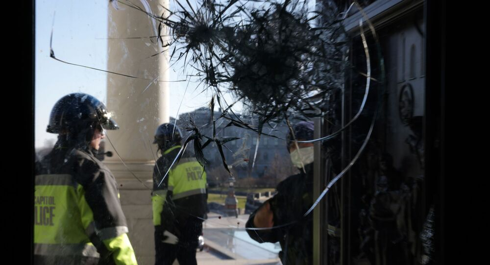 Members of U.S. Capitol Police inspect a damaged entrance of the U.S. Capitol January 7, 2021 in Washington, DC.