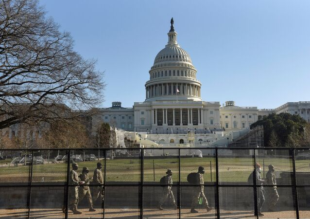 National Guard members walk behind a fence installed in front of the U.S. Capitol, a day after supporters of U.S. President Donald Trump occupied the Capitol building, in Washington, U.S. January 7, 2021.