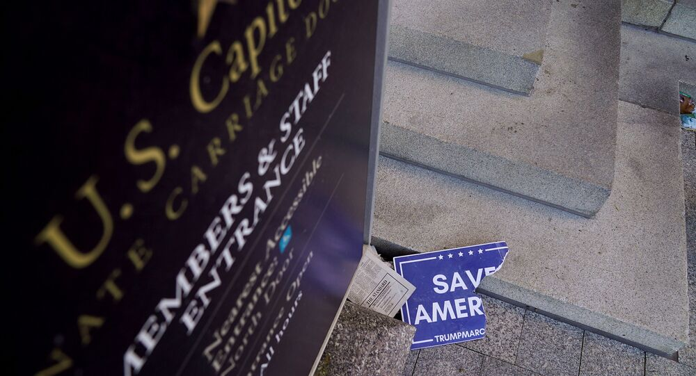 Scraps of a demonstrator's poster lays below a Congressional members and staff entrance sign at the Senate Carriage Entrance of the U.S. Capitol a day after hundreds of supporters of U.S. President Donald Trump occupied the Capitol in Washington, U.S., January 7, 2021.