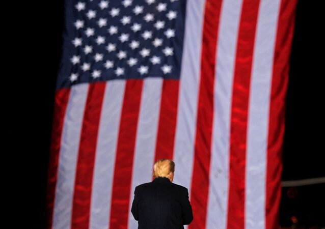 U.S. President Donald Trump stands in front of a U.S. flag while campaigning for Republican Senator Kelly Loeffler on the eve of the run-off election to decide both of Georgia's Senate seats, in Dalton, Georgia, U.S., January 4, 2021.