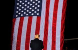 US President Donald Trump stands in front of the stars and stripes while campaigning for Republican Senator Kelly Loeffler on the eve of the run-off election to decide both of Georgia's Senate seats, in Dalton, Georgia, US, 4 January 2021.