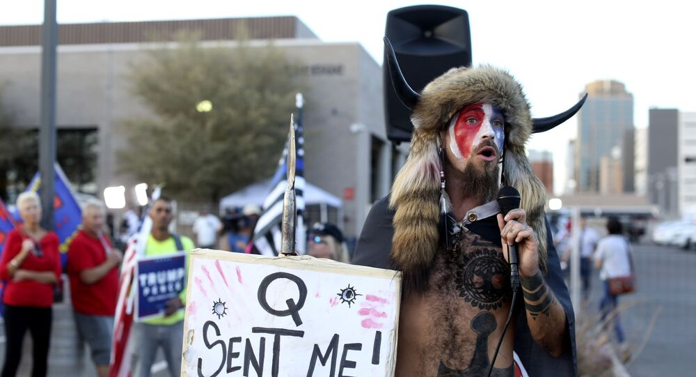 A Qanon believer speaks to a crowd of President Donald Trump supporters outside of the Maricopa County Recorder's Office where votes in the general election are being counted, in Phoenix, Thursday, Nov. 5, 2020.