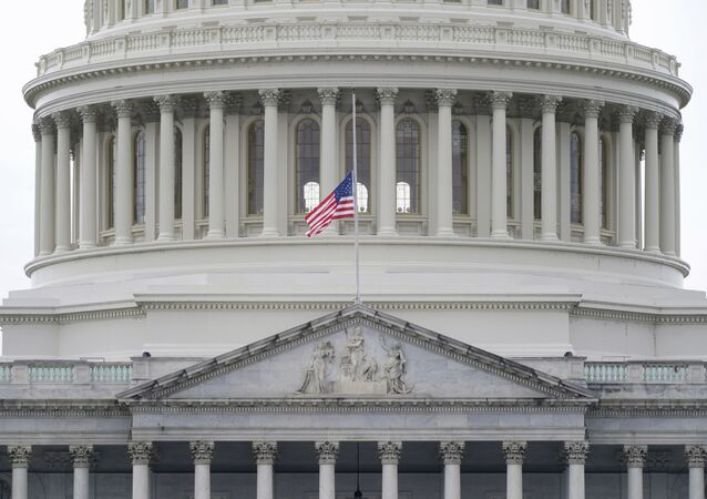 An American flag flies at half-staff in remembrance of U.S. Capitol Police Officer Brian Sicknick above the Capitol Building in Washington, Friday, Jan. 8, 2021