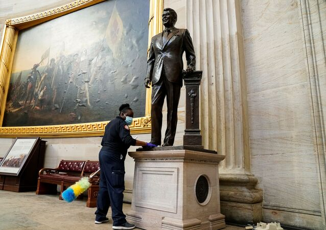 A worker cleans a statue of former President Ronald Reagan inside the Rotunda of the U.S. Capitol a day after supporters of U.S. President Donald Trump stormed the Capitol in Washington, U.S., January 7, 2021.