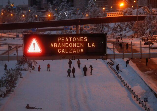 A sign displays a message reading Pedestrians leave the road as people play in the snow on the M-30 motorway, in Madrid, Spain, January 9, 2021.