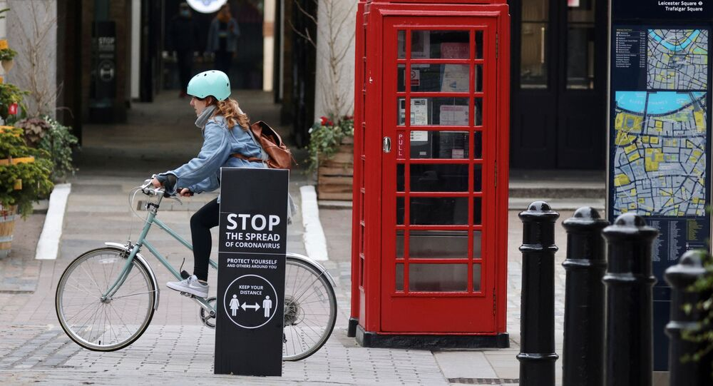 A woman rides a bike past a warning sign in Covent Garden amid the coronavirus disease (COVID-19) pandemic in London, Britain, January 10, 2021.