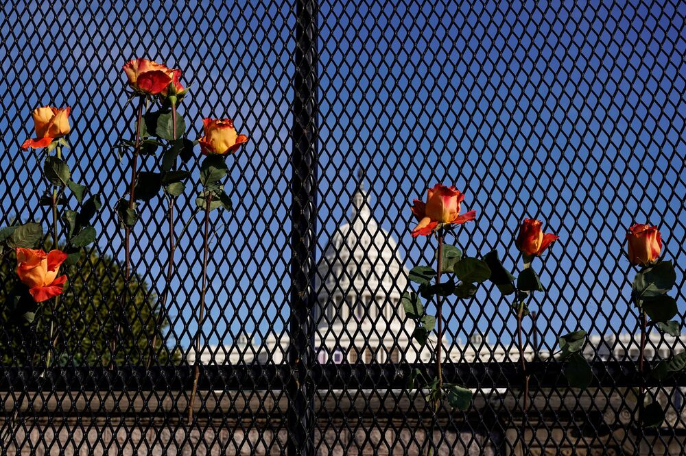 Flowers are placed in security fencing days after supporters of US President Donald Trump besieged the US Capitol in Washington, 10 January 2021.