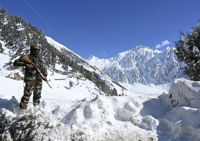 An Indian army soldier stands on a snow covered road after snowfall near Zojila mountain pass that connects Srinagar to the union territory of Ladakh, bordering China on November 26, 2020