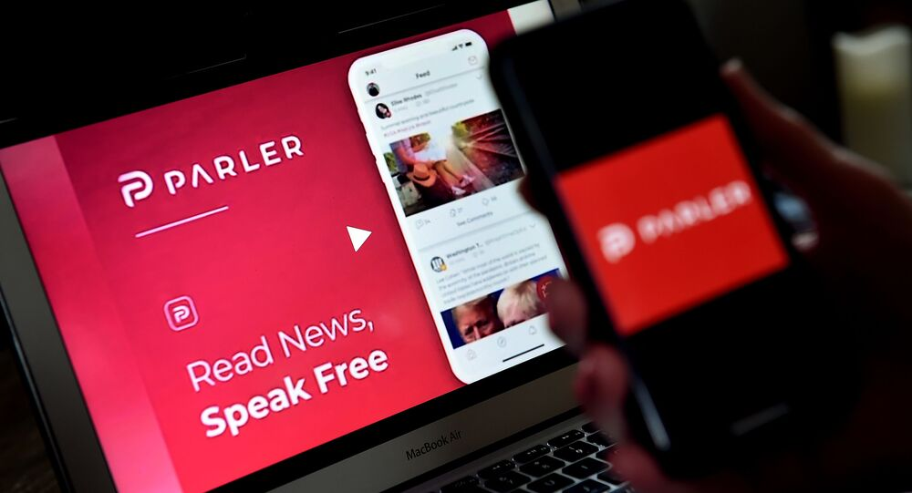 (FILES) In this file photo taken on July 01, 2020 an illustration picture shows social media application logo from Parler displayed on a smartphone with its website in the background in Arlington, Virginia. - Apple on January 9, 2021