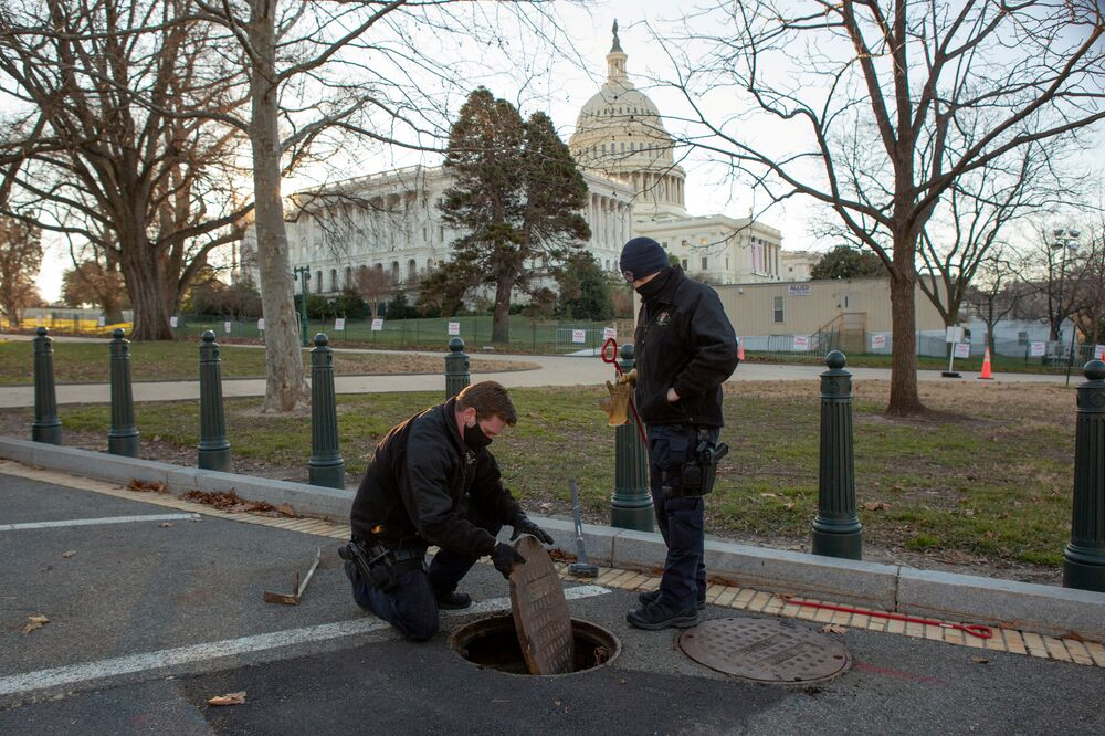 US Capitol Police officers from the Hazardous Devices Section inspect and seal a manhole on the grounds of the US Capitol in Washington, 10 January 2021.