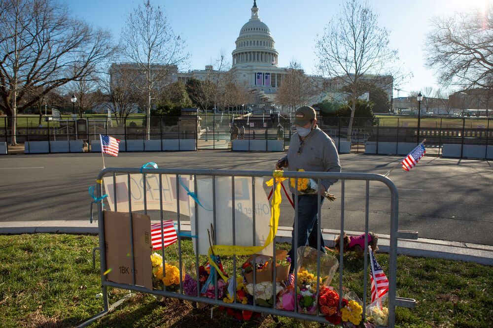 Sal Gonzalez places flowers at a memorial to honour slain Capitol Police officer Brian Sicknick on the west side of the US Capitol building in Washington, 10 January 2021.