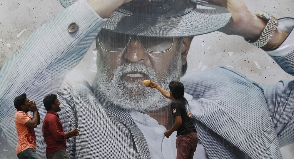 Indian superstar Rajinikanth's fans pray in front of his poster outside a cinema where his Tamil-language blockbuster Kabali is being shown, in Chennai, India, Friday, 22 July 2016.
