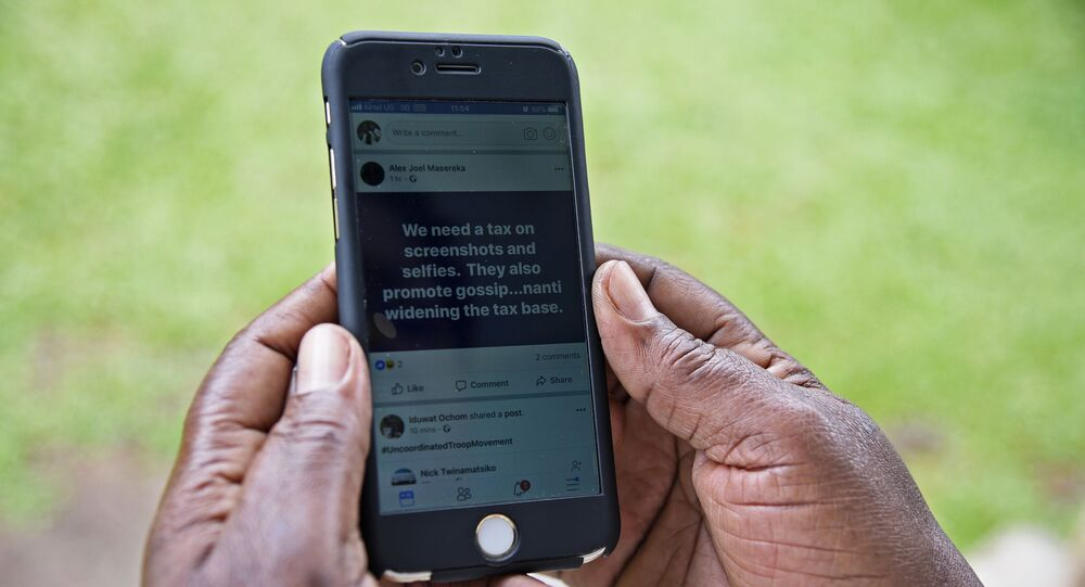 A woman reads a message on social media tax as she scrolls through her Facebook account on her phone in Kampala on July 5, 2018